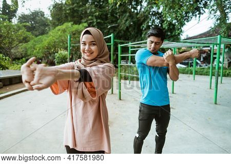 An Asian Young Man And A Girl In A Veil Standing Doing Warm-up Movements Before Exercising
