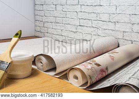 Multicolored Patterned Wallpaper, Brush, Glue Are Prepared For Home Interior Renovation. Home Renova