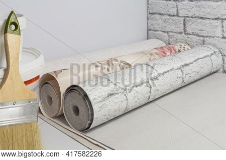 Multicolored Rolls Of Wallpaper, Brush, Glue, Paint Ready For Renovation In The Apartment Room. Do-i