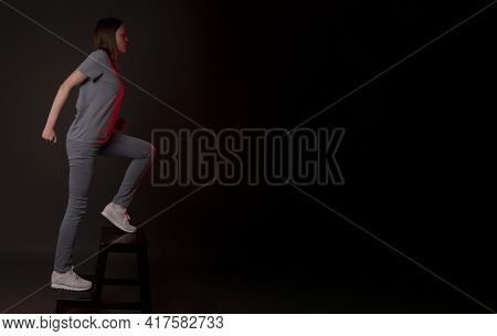 Young Woman Walking Up Stairs, Running Upstairs On Black Background. Concept Of Aspirations, Self Gr