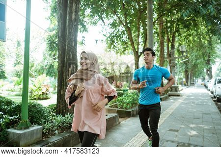 An Asian Young Man And A Girl In A Veil Doing Jogging Together