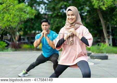 Hijab Girls Doing Leg Warm-up Exercises Together