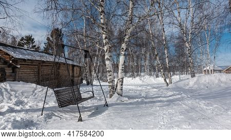On The Ground Covered With Snow, Paths Are Trodden, Nearby Are Snowdrifts. There Is A Wooden Swing -