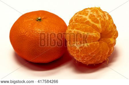 Two Tangerines Or Tangerine Fruits, One Peeled, The Other Not. White Background, Close-up, Free Spac