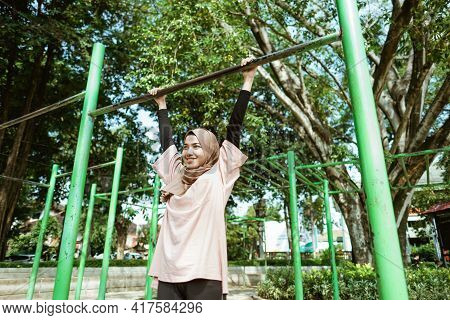 A Girl In Veil Doing Pull Up To Improve Lung Ability And Lose Weight By Exercising Outdoors