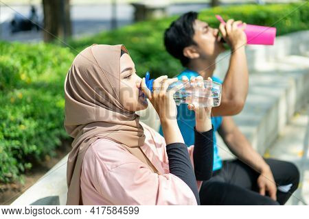A Girl In A Veil And A Young Man Sit Drinking With A Bottle After Doing Outdoor Sports