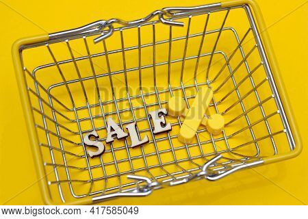 The Word Sale Is Laid Out In Letters On The Bottom Of The Small Shopping Basket. The Percent Sign Is