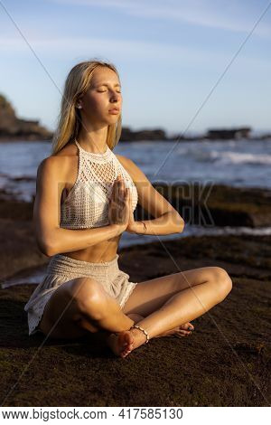Attractive Woman Practicing Yoga On The Beach. Sitting In Padmasana, Lotus Pose. Hands In Namaste Mu