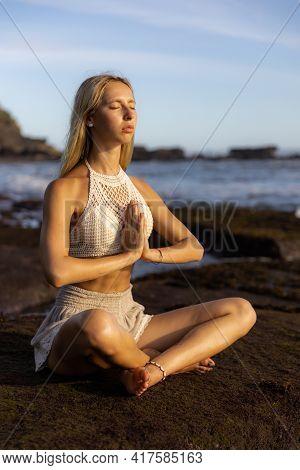 Beautiful Woman Practicing Yoga On The Beach. Sitting In Padmasana, Lotus Pose. Hands In Namaste Mud