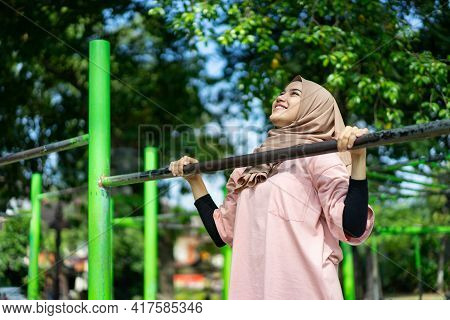 An Asian Girl In A Veil Does Pull Ups To Work Out Her Hand Muscles