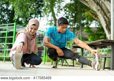 A Man And A Girl In A Veil In Gym Clothes Doing The Leg Warm-up Movement Together