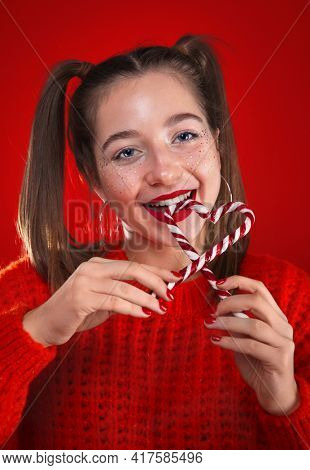 Pretty girl eating colourful sweet christmas candy sticks in a heart form. Happy smiling teenager with makeup over red background.