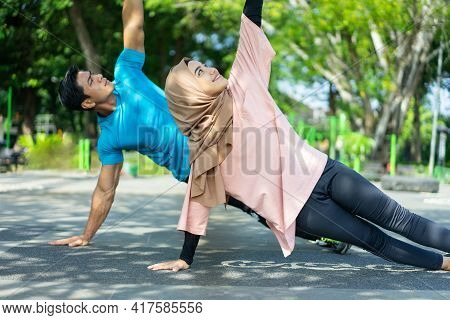 A Man And A Girl In A Veil In Gym Clothes Doing Hand Exercises