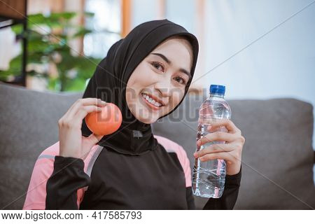 Close Up Of An Asian Woman In A Veil Sportswear Smiles While Holding A Drinking Bottle With Hand Ges