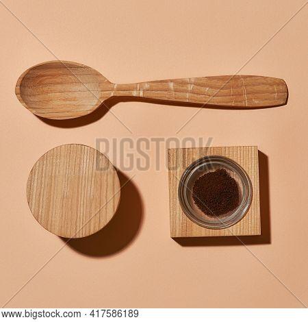 Organic Exfoliating Scrub Next To Wooden Spoon On Light Orange Background, Flat Lay, Top View. Beaut