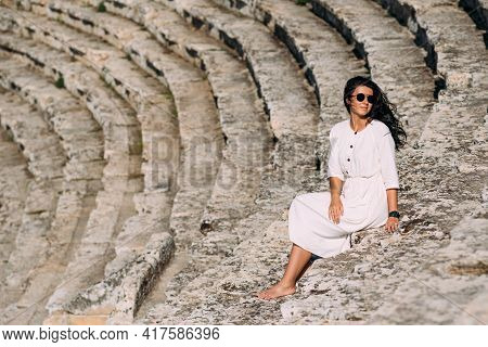 A Stylish Young Woman In A Dress Sits On The Steps On A Sunny Bright Summer Day. Portrait Of A Beaut