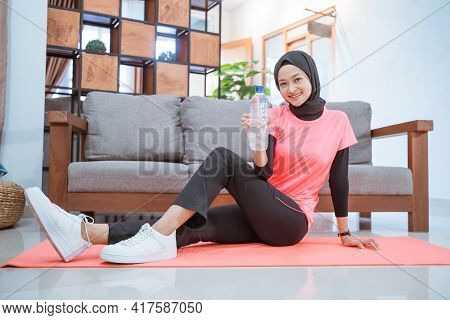 Asian Girl In A Veil Sportswear Smiles While Holding A Drinking Bottle While Sitting On The Floor Wi