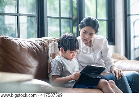 Asian Mother Teaching His Young Son For Lesson On E-learning Classes In Tablet At Home. The Boy Usin