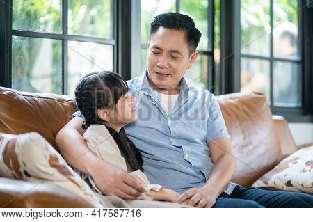 Asian Father Spending Time With Little Kid Daughter, Sitting On Sofa At Home. Attractive Parent Talk