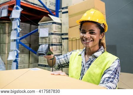 Young Smiling Black Woman Worker In Safety Helmet And Vest Checking Box In Stock In Clean Factory Wa