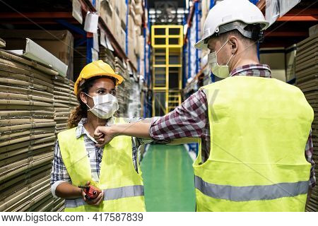 Two Colleague Female And Male Workers In Warehouse Factory Have A Greeting By Touching The Elbow Or