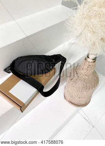 New Black Sling Or Hip Bag On The Blank Cardboard Box