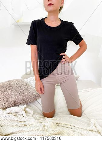 Beautiful Young Woman In Bed Wearing Knee Length Leggings And T-shirt