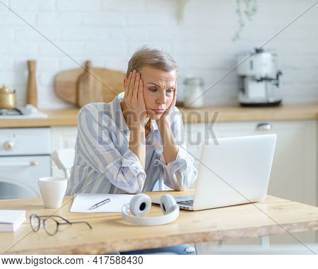 Stressed Mature Woman In Casual Wear Sitting In Modern Kitchen, Holding Head In Hands And Looking On
