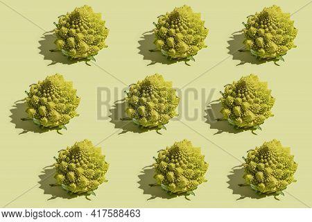 Hard Light Pattern Of Green Romanesco Cabbage On Green Surface