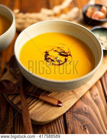 One Grey Bowl Of Pumpkin Cream Soup With Pumpkin Seed Oil On Wooden Table And Two Wooden Spoons