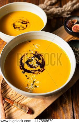 Two Grey Bowls With Pumpkin Cream Soup With Pumpkin Seed Oil On Wooden Table
