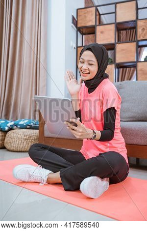 A Girl In A Veil Gym Outfit With A Smile Looking At A Tablet With A Hand Gesture Of Say Hello