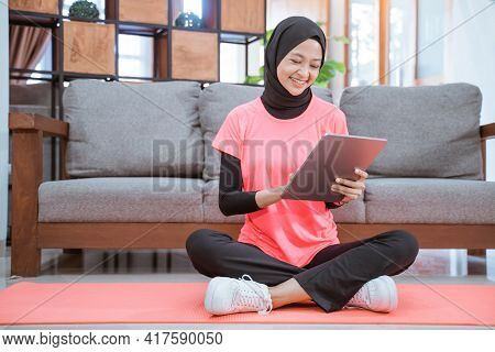 Asian Girl In A Veil Gym Outfit With A Smile Looking At A Tablet Before Indoor Exercise
