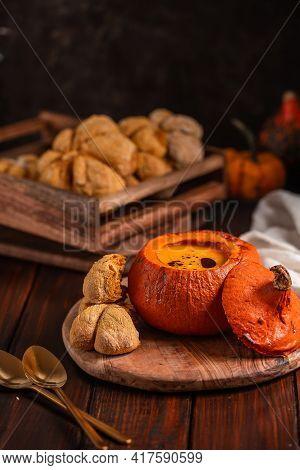 Pumpkin Cream Soup In Pumpkin With Pumpkin-shaped Buns On Black Background