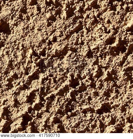 Seamless Texture. Rough Brown Background. Clay Soil Illuminated By The Sun. Textured Natural Backgro