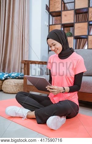 Asian Girl In A Veil Gym Outfit With A Smile Looking At A Tablet When Sitting On The Floor With A Ma