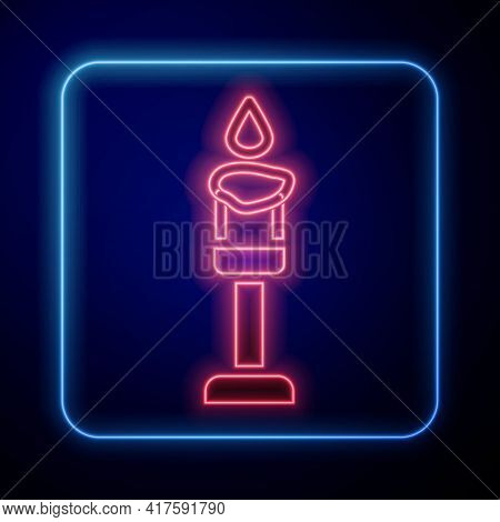 Glowing Neon Burning Candle Icon Isolated On Blue Background. Cylindrical Aromatic Candle Stick With