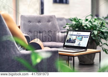 Laptop With News Website In Screen On Table In Business Office, Corporate Lounge Or Hotel Lobby. Com