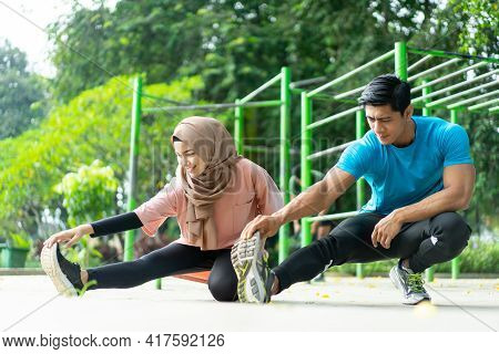 A Young Man And A Girl In A Head Scarf Doing Some Warm-up Exercises Together