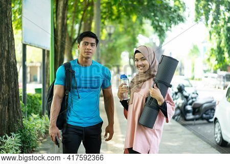 A Girl In A Headscarf Brings A Mattress And A Water Bottle And A Man Carrying A Backpack Smiles As H