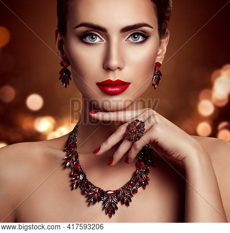 Beauty Woman Face Makeup And Jewelry, Fashion Model Portrait With Jewellery Over Shining Lights Back