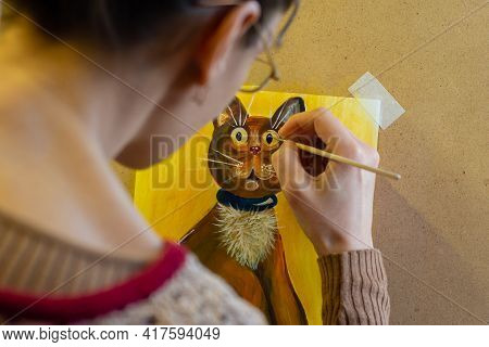 The Artist Paints A Drawing Of A Cat On An Easel With Acrylic Paints, A View From The Artist's Back