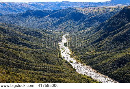 River Flowing Through Steep Tree Lined Valley