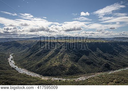 Meandering River Flowing Through Steep Tree Lined Valley