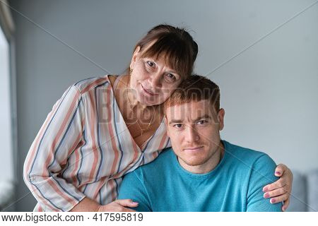 Cheerful Elderly Woman Sitting On The Sofa Next To His Adult Son. Caring Son Hugs His Elderly Mother