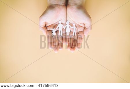 Hand Holding Family Paper Cut On Yellow Background. Family Day Concept, Foster Care, Domestic Violen