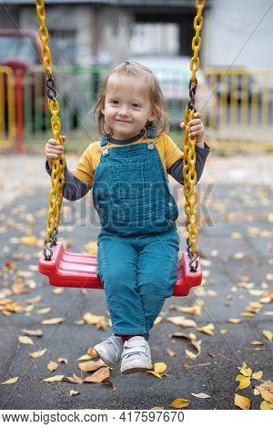 Happy Little Girl Having Fun On Outdoor Playground. Swinging On Swing.
