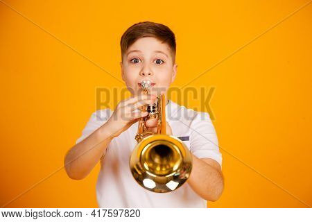 A Boy Plays The Trumpet. Beautiful Teenager Boy Plays Trumpet Musical Instrument