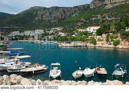 Kas, Turkey - 16 October, 2019: Small boats in marina and rocky mountains on Turkish Mediterranean coast, Popular tourist destination