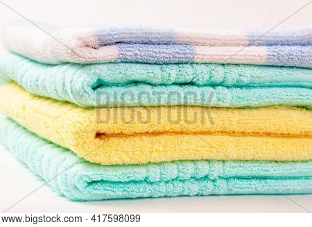 A Stack Of Multi-colored Terry Towels Folded In A Pile